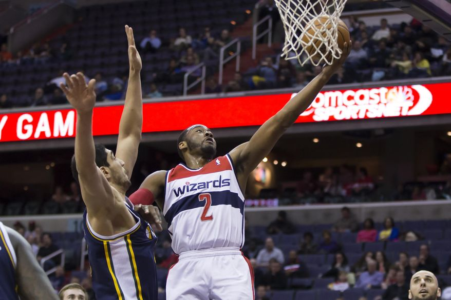 Washington Wizards point guard John Wall (2) drives to the basket against Utah Jazz center Enes Kanter during the first half of an NBA basketball game on Wednesday, March 5, 2014, in Washington. (AP Photo/ Evan Vucci)