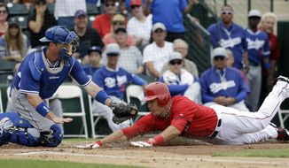 Los Angeles Dodgers catcher A.J. Ellis tags out Los Angeles Angels' Mike Trout at home during the first inning of an exhibition spring training baseball game Thursday, March 6, 2014, in Tempe, Ariz. Trout tried to stretch a triple into an inside the park home run. (AP Photo/Morry Gash)