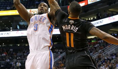 Oklahoma City Thunder forward Serge Ibaka, of the Republic of the Congo, shoots over Phoenix Suns' Markieff Morris (11) during the first half of an NBA basketball game on Thursday, March 6, 2014, in Phoenix. (AP Photo/Matt York)