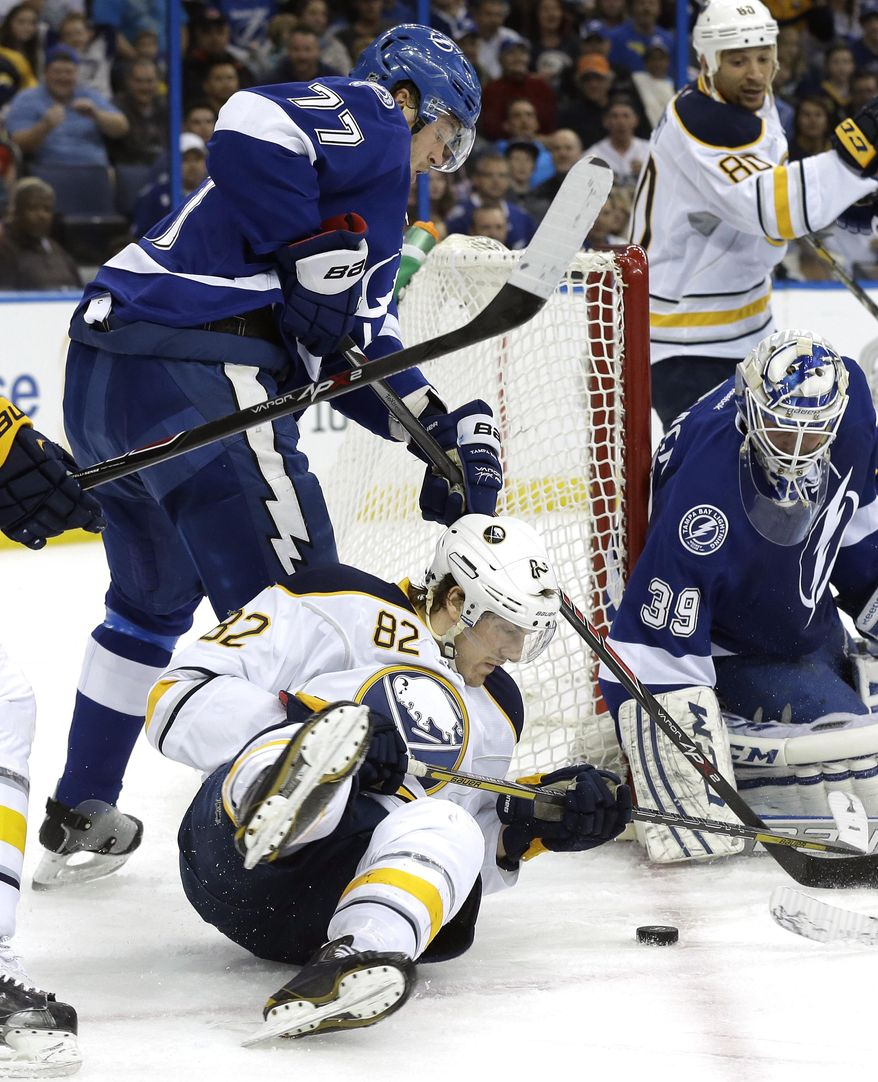Buffalo Sabres left wing Marcus Foligno (82) looks for the puck after getting knocked down by Tampa Bay Lightning defenseman Victor Hedman (77), of Sweden, in front of goalie Anders Lindback (39), of Sweden, during the first period of an NHL hockey game Thursday, March 6, 2014, in Tampa, Fla. (AP Photo/Chris O'Meara)