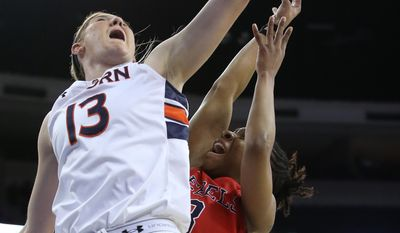 Mississippi guard Valencia McFarland (3) has her shot blocked by Auburn guard/forward Katie Frerking (13) in the first  half of a second-round women's Southeastern Conference tournament NCAA college basketball game on Thursday, March 6, 2014, in Duluth, Ga.  (AP Photo/Jason Getz)