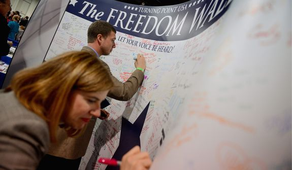 Photographs by Andrew Harnik/The Washington TimesDavid Eber of Lansdowne, Va., and Virginia Haynes sign the Freedom Wall at the Gaylord National Resort and Convention Center.