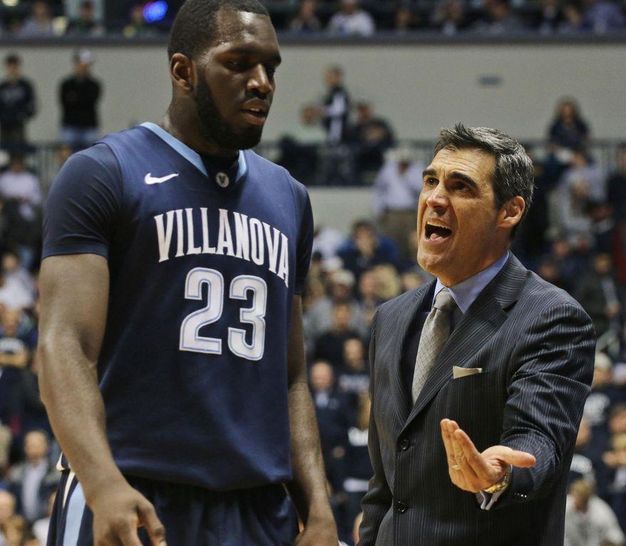 Villanova coach Jay Wright talks with Daniel Ochefu during the first half of an NCAA college basketball game against Xavier in Cincinnati on Thursday, March 6, 2014. (AP Photo/Tom Uhlman)