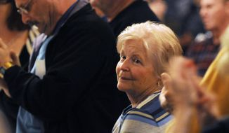 This Feb. 26, 2013 photo shows Mary Shepard, who survived a brutal attack in 2009 by an intruder while working at her church in Anna, Ill., receiving a standing ovation during a concealed carry meeting in Cobden, Ill. Shepard, who fought the state's ban on carrying concealed weapons after she was attacked, now has her permit to have a handgun in public. Shepard sued to have the state's ban thrown out, and her efforts contributed to the concealed carry law passed last July.  She argues that had she not been barred from carrying a gun, she could have thwarted the attack. (AP Photo/The Southern, Aaron Eisenhauer)