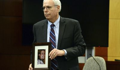 Chief Deputy District Attorney John Topolnicki holds up a photo of Eric Autobee, a corrections officer who the prosecutor said was fatally attacked by Edward Montour, during opening arguments in Douglas County District Court, Wednesday, March 5, 2014, in Castle Rock. Colo. Montour was serving a life sentence for the 1997 death of his 11-week-old daughter when prosecutors say he beat to death Autobee in 2002. He pleaded not guilty by reason of insanity, and prosecutors are seeking the death penalty.  (AP Photo/The Denver Post, RJ Sangosti, Pool)