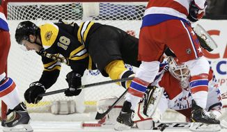 Boston Bruins right wing Reilly Smith (18) gets tripped up as Washington Capitals goalie Braden Holtby, right, makes a save during the first period of an NHL hockey game, Thursday, March 6, 2014, in Boston. (AP Photo/Charles Krupa)