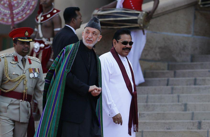 Sri Lankan President Mahinda Rajapaksa, right, and Afghan President Hamid Karzai walk together during an official reception for Karzai in Colombo, Sri Lanka, Thursday, March 6, 2014. Karzai is on a three-day official visit to Sri Lanka. (AP Photo/Eranga Jayawardena)