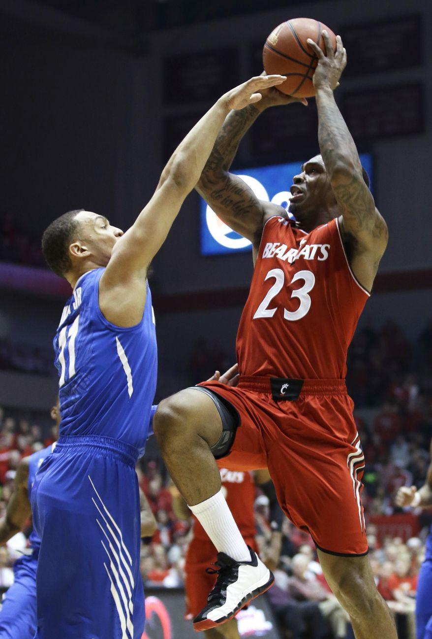 Cincinnati guard Sean Kilpatrick (23) shoots against Memphis guard Michael Dixon Jr. in the first half of an NCAA college basketball game, Thursday, March 6, 2014, in Cincinnati. (AP Photo/Al Behrman)