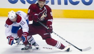 Phoenix Coyotes' Antoine Vermette, right, shoots in front of Montreal Canadiens' David Desharnais in the first period of an NHL hockey game on Thursday, March 6, 2014, in Glendale, Ariz. (AP Photo/The Arizona Republic, Patrick Breen) MARICOPA COUNTY OUT; NO SALES