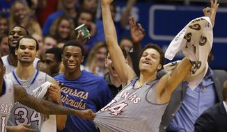 Kansas forward Perry Ellis (34), guard Andrew Wiggins, middle, and guard Brannen Greene (14) celebrate a teammate's 3-point basket during the second half of an NCAA college basketball game against Texas Tech in Lawrence, Kan., Wednesday, March 5, 2014. Kansas defeated Texas Tech 82-57. (AP Photo/Orlin Wagner)