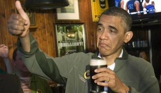 President Obama gives the thumbs up while holding a beer.
