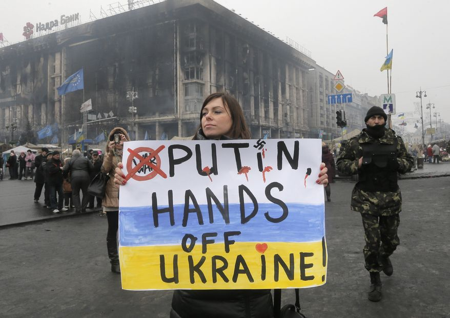 A woman holds a poster against war at Kiev's Independence Square, in Ukraine, Thursday, March 6, 2014. The  Heads of State of the EU will meet Thursday in emergency session in Brussels to discuss the situation in Ukraine. The destroyed trade union offices which was burned in clashes seen in the background  (AP Photo/Efrem Lukatsky)