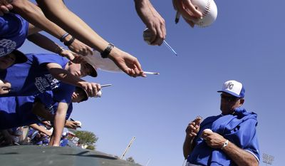 Kansas City Royals' George Brett signs autographs for fans before a spring training baseball game against the San Francisco Giants, Friday, March 7, 2014, in Surprise, Ariz. (AP Photo/Tony Gutierrez)