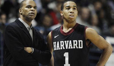 Harvard head coach Tommy Amaker, left, talks with player Siyani Chambers during the first half of an NCAA college basketball game, Friday, March 7, 2014, in New Haven, Conn. (AP Photo/Jessica Hill)