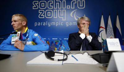 Ukrainian paralympic athlete Grygorii Vovchinskyi shows his credential as President of the National Paralympic Committee of Ukraine Valeriy Sushkevich puts his hands to his face during a press conference ahead of the opening ceremony of the 2014 Winter Paralympics in Sochi, Russia, Friday, March 7, 2014. (AP Photo/Pavel Golovkin)
