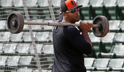 Baltimore Orioles' Nelson Cruz carries a set of wheels for a backstop off the practice field after infield practice at Ed Smith Stadium before an exhibition spring training baseball game against the Philadelphia Phillies in Sarasota, Fla., Friday, March 7, 2014. (AP Photo/Gene J. Puskar)