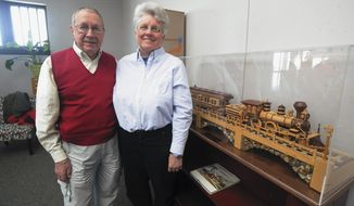 In this Feb. 12, 2014 photo, Fred and Gretchen Decker pose with the detailed, handcrafted wooden train they donated to the Mattoon Arts Council and city Department of Tourism and Arts. It's seen on display at their offices at the Illinois Central Railroad Depot in Mattoon, Ill. (AP Photo/Journal Gazette, Kevin Kilhoffer)