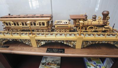 In this Feb. 12, 2014 photo, a detailed, handcrafted wooden train, donated by Fred and Gretchen Decker to the Mattoon Arts Council and city Department of Tourism and Arts and is seen on display at their offices at the Illinois Central Railroad Depot in Mattoon, Ill. (AP Photo/Journal Gazette, Kevin Kilhoffer)
