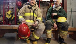 In this Feb. 25, 2014 photo, Paradise Valley Fire Department Rural Firefighters Richard Johnson, left, and his neighbor, Greg Lynch, talk at the Paradise Valley Fire Department in Park County, Mont. (AP Photo/Livingston Enterprise, Shawn Raecke)