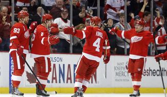 Detroit Red Wings' Brendan Smith (2) celebrates his first period goal with teammates Johan Franzen (93), of Sweden, Jakub Kindl (4), of Czechoslovakia, and Gustav Nyquist, right, of Sweden, during the first period of an NHL hockey game against the New Jersey Devils Friday, March 7, 2014, in Detroit. (AP Photo/Duane Burleson)