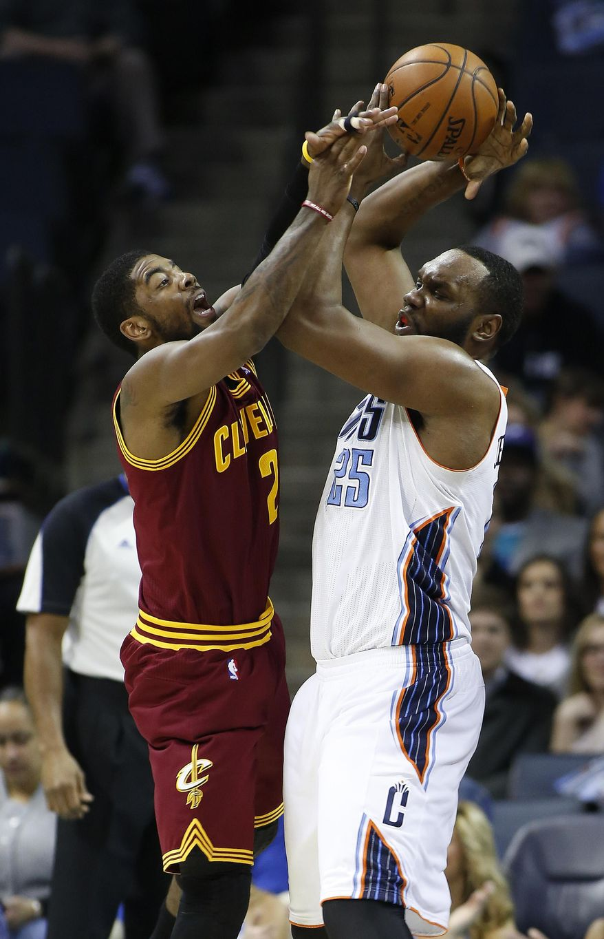 Cleveland Cavaliers guard Kyrie Irving, left, tries to disrupt Charlotte Bobcats center Al Jefferson's pass during the first half of an NBA basketball game in Charlotte, N.C., Friday, March 7, 2014. (AP Photo/Nell Redmond)