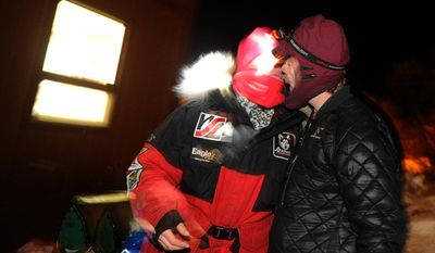 Musher Aliy Zirkle gets a kiss from her husband and fellow Iditarod musher Allen Moore as she prepares to leave the Takotna checkpoint at 9 P.M. during the 2014 Iditarod Trail Sled Dog Race on Wednesday, March 5, 2014.(AP Photo/The Anchorage Daily News, Bob Hallinen)  LOCAL TV OUT (KTUU-TV, KTVA-TV) LOCAL PRINT OUT (THE ANCHORAGE PRESS, THE ALASKA DISPATCH)