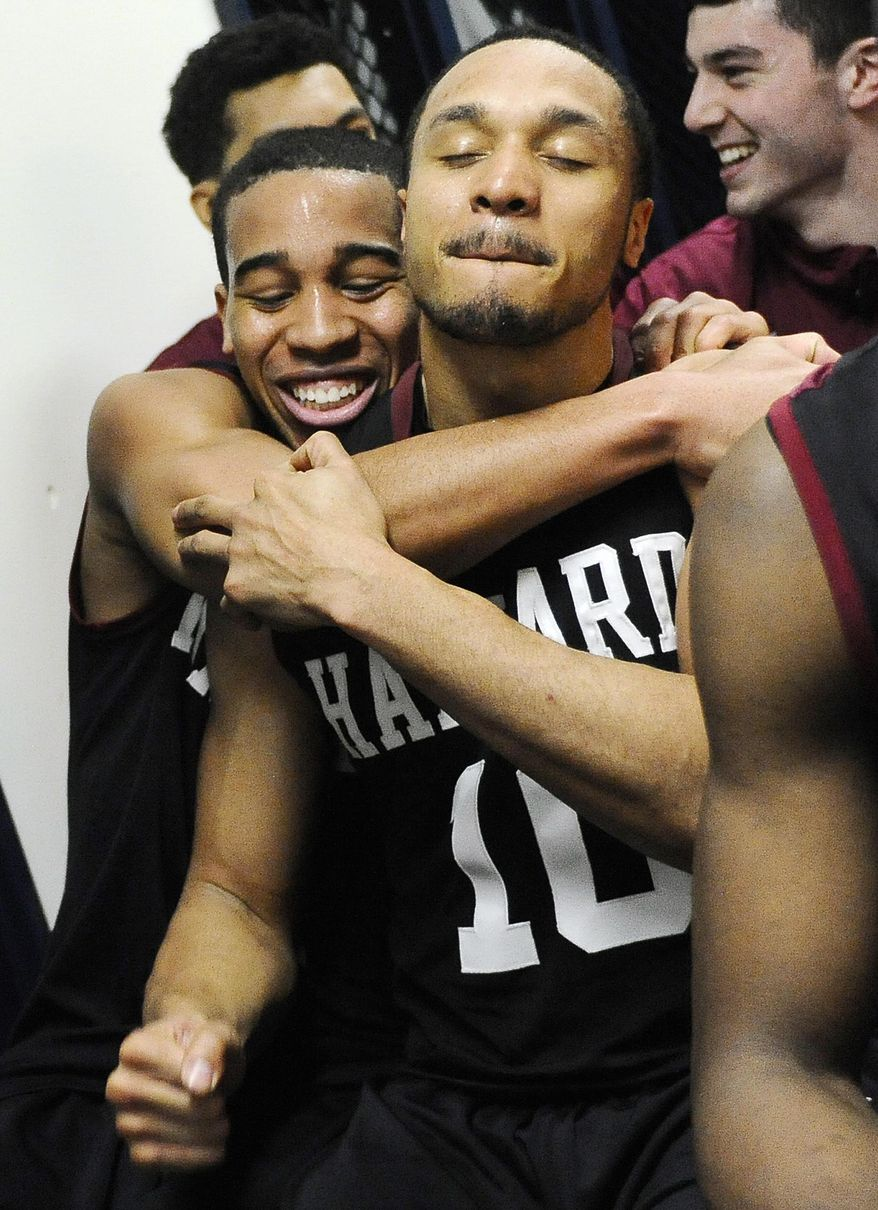 Harvard's Siyani Chambers, left, and Brandyn Curry, right, embrace in the locker room after their 70-58 win over Yale at the end of an NCAA college basketball game, Friday, March 7, 2014, in New Haven, Conn. (AP Photo/Jessica Hill)