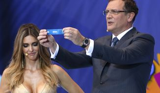 FIFA Secretary General Jerome Valcke shows the ticket of Russia during the draw ceremony for the 2014 soccer World Cup in Costa do Sauipe near Salvador, Brazil, Friday, Dec. 6, 2013. (AP Photo/Andre Penner)