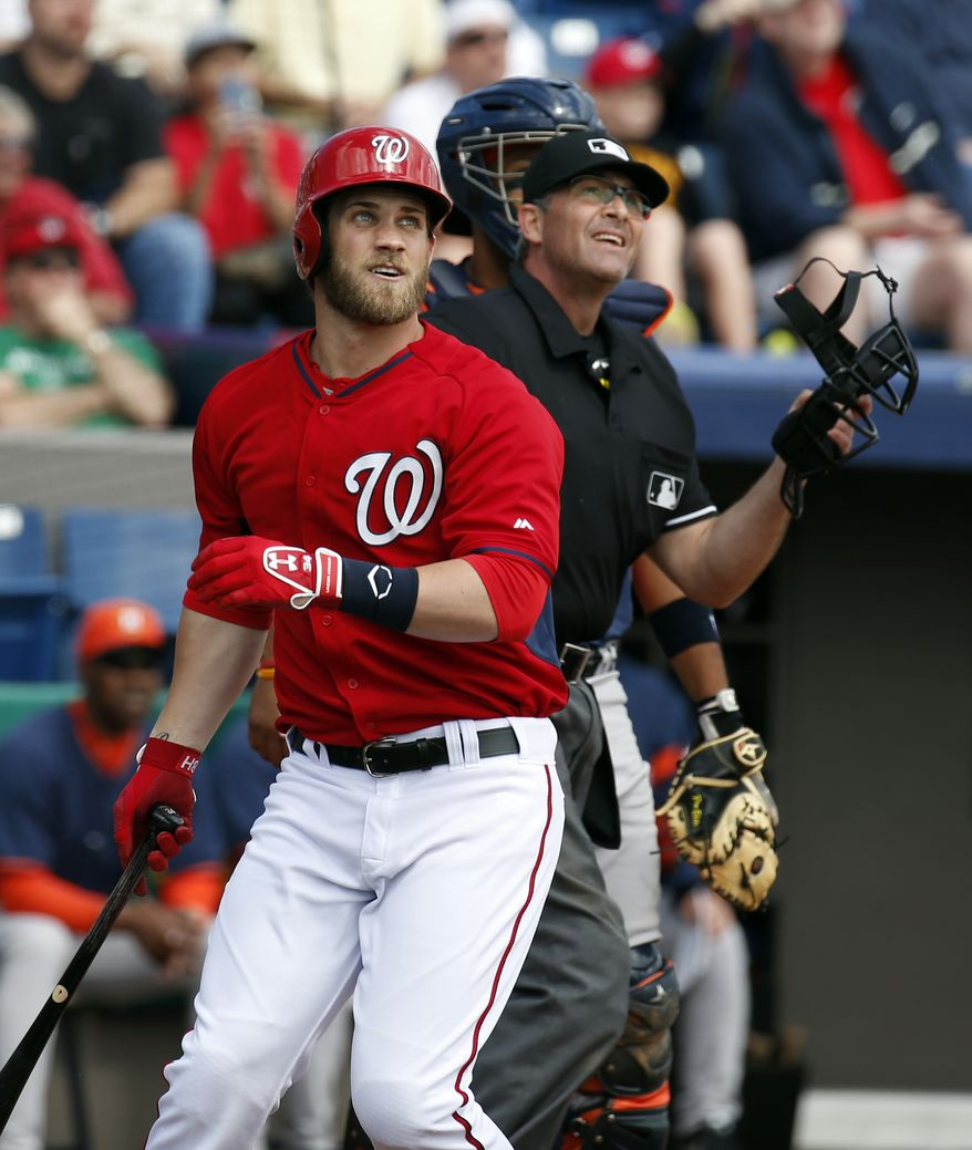Washington Nationals' Bryce Harper, left, watches his two-run homer with home plate umpire Paul Nauert in the first inning of a spring exhibition baseball game against the Houston Astros, Friday, March 7, 2014, in Viera, Fla. (AP Photo/Alex Brandon)