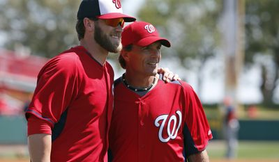 Washington Nationals left fielder Bryce Harper, left, poses for a photograph with former NFL quarterback Doug Flutie, after Flutie threw out a ceremonial first pitch before a spring exhibition baseball game against the Houston Astros, Friday, March 7, 2014, in Viera, Fla. (AP Photo/Alex Brandon)