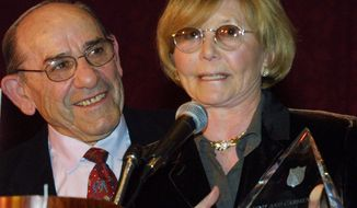 "FILE- In this Dec. 6, 2000 file photo, Baseball Hall-of-Famer Yogi Berra listens as his wife Carmen accepts the ""Pinnacle of Achievement"" award at the Salvation Army Association of Greater New York's Annual Luncheon in New York. According to NJ.com, Dave Kaplan, the director of the Yogi Berra Museum and Learning Center, said that Carmen Berra died of complications from a stroke on Thursday, March 6, 2014. She was 85.  (AP Photo/Shawn Baldwin, File)"