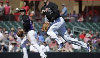 Colorado Rockies shortstop Troy Tulowitzki, right, throws Los Angeles Angels' Ian Stewart out at first as third baseman Nolan Arenado looks on during the first inning of a spring training baseball game in Scottsdale, Ariz., Friday, March 7, 2014. (AP Photo/Chris Carlson)