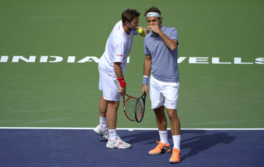 Roger Federer, of Switzerland, right, and doubles partner Stanislas Wawrinka, of Switzerland, talk during a match at the BNP Paribas Open tennis tournament against Rohan Bopanna, of India, and Aisam-Ul-Haq Qureshi, of Pakistan,  Friday, March 7, 2014 in Indian Wells, Calif. (AP Photo/Mark J. Terrill)
