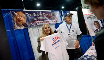 Tara Nolan, left, and and David Fischer, second from left,  work at the National Draft Ben Carson for President Committee booth at the Conservative Political Action Conference (CPAC) held at the Gaylord Hotel, National Harbor, Md., Friday, March 7, 2014. (Andrew Harnik/The Washington Times)