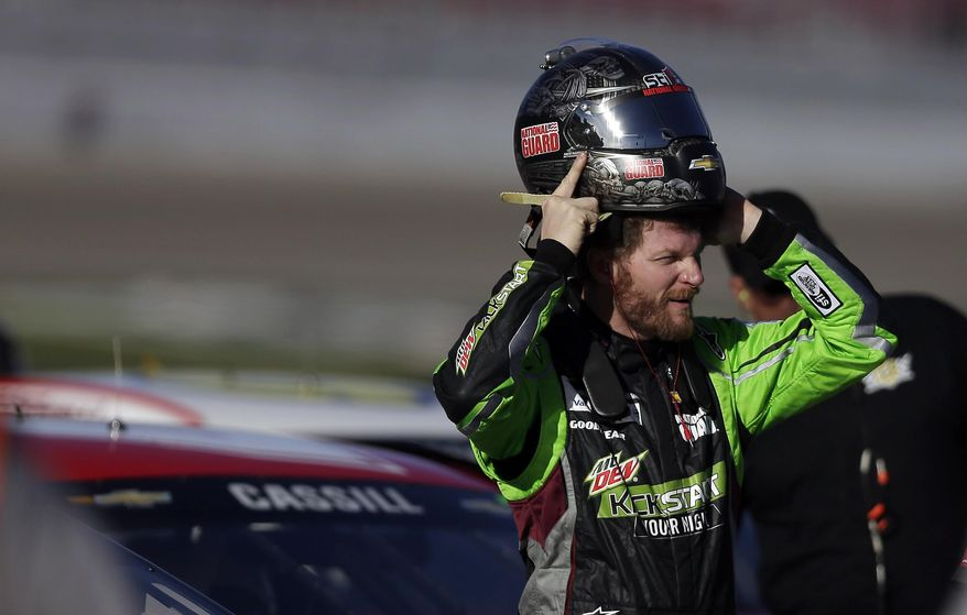 Dale Earnhardt Jr. puts on his helmet during qualifying for Sunday's NASCAR Sprint Cup Series auto race on Friday, March 7, 2014, in Las Vegas. (AP Photo/Isaac Brekken)