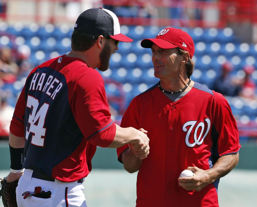 Washington Nationals left fielder Bryce Harper greets former NFL quarterback Doug Flutie, after Flutie threw out a ceremonial first pitch before a spring exhibition baseball game against the Houston Astros, Friday, March 7, 2014, in Viera, Fla. (AP Photo/Alex Brandon)