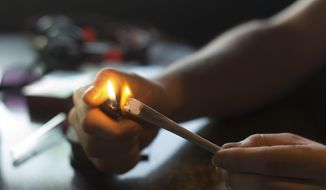 In this photo taken Friday, Dec. 20, 2013, a visitor lights a marijuana joint in coffee shop Mississippi in Maastricht, southern Netherlands. While several U.S. states have moved to legalize the sale of marijuana, the Netherlands is going in the opposite direction, clamping down on its famed tolerance policy toward weed. In Maastricht, attempts to ban foreigners from buying weed have led to a resurgence of street-dealers, while Amsterdam is shutting marijuana cafes located too close to schools. (AP Photo/Ermindo Armino)