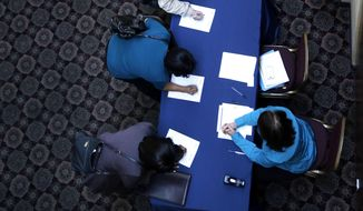 In this Wednesday, Jan. 22, 2014, photo, job seekers line up to sign in before meeting prospective employers at a career fair at a hotel in Dallas. The Labor Department releases employment data for February, on Friday, March, 7, 2014. (AP Photo/LM Otero)