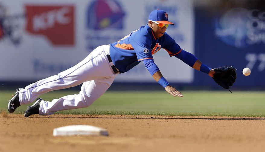 New York Mets shortstop Wilfredo Tovar dives but cannot reach a ball hit for a single by St. Louis Cardinals' Ed Easley during the seventh inning of an exhibition spring training baseball game Friday, March 7, 2014, in Port St. Lucie, Fla. (AP Photo/Jeff Roberson)
