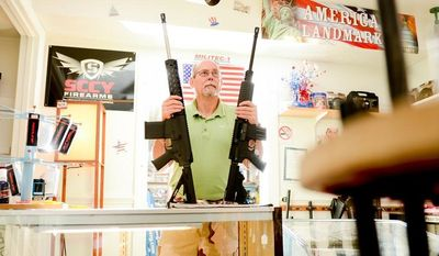 Jim Greer, owner of Angus MacGregor's Trading Post, poses with two AR-15 assault rifles at his store, Waldorf, Md., Thursday, September 12, 2013. Greer is moving his gun shop and model train store to Pennsylvania because of Maryland's new gun legislation starting next month. (Andrew Harnik/The Washington Times)