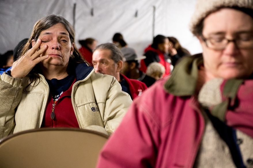 Debbie May of Buena Vista, Va., left, waits in a warming tent in the cold pre-dawn hours to be let into the Remote Area Medical's facilities to be seen by a doctor at Southern Virginia University, Buena Vista, Va., Saturday, March 1, 2014. Remote Area Medical Volunteer Corps (RAM) is a Knoxville, Tennessee-based, non-profit, volunteer, airborne medical relief corps that provides free health care, dental care, eye care, veterinary services, and technical and educational assistance to people in remote areas of the United States, and around the world for people that need it. (Andrew Harnik/The Washington Times)