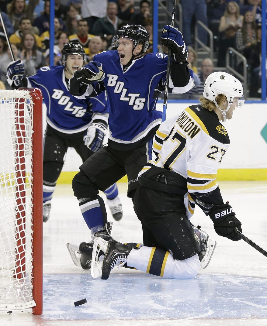 Tampa Bay Lightning left wing Ondrej Palat, center, of the Czech Republic, celebrates his goal with teammate Tyler Johnson, left, against Boston Bruins defenseman Dougie Hamilton (27) during the second period of an NHL hockey game on Saturday, March 8, 2014, in Tampa, Fla. (AP Photo/Chris O'Meara)