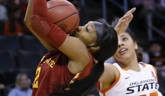 Iowa State guard Seanna Johnson (12) grabs a rebound in front of Oklahoma State guard Brittney Martin (22) in the second half of an NCAA college basketball game in the quarterfinals of the Big 12 Conference women's college tournament in Oklahoma City, Saturday, March 8, 2014. Oklahoma State won 67-57. (AP Photo/Sue Ogrocki)