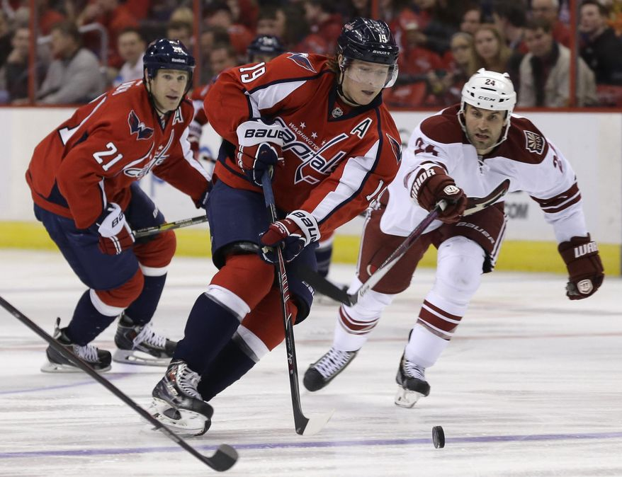 Washington Capitals center Nicklas Backstrom (19), and Phoenix Coyotes center Kyle Chipchura (24) skate for the puck during the first period of an NHL hockey game, Saturday, March 8, 2014, in Washington. At left is Capitals center Brooks Laich. (AP Photo/Carolyn Kaster)