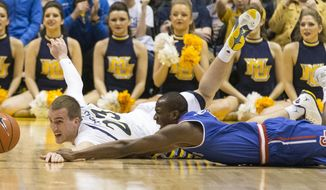 Marquette's Jake Thomas, left, hits the floor along with St. John's Phil Greene IV as the battle for a loose ball in the second half of an NCAA college basketball game Saturday, March 8, 2014, in Milwaukee. (AP Photo/Tom Lynn)