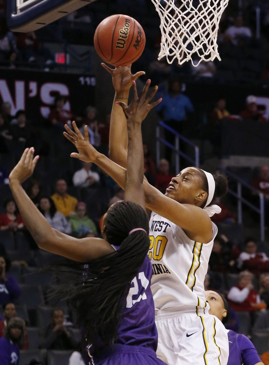 West Virginia center Asya Bussie (20) shoots as TCU center Latricia Lovings (21) defends in the first half of an NCAA college basketball game in the quarterfinals of the Big 12 Conference women's tournament in Oklahoma City, Saturday, March 8, 2014. West Virginia won 67-59. (AP Photo/Sue Ogrocki)