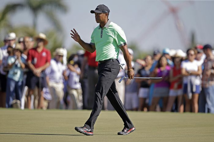 Tiger Woods acknowledges the gallery after making par on the 17th hole during the third round of the Cadillac Championship golf tournament Saturday, March 8, 2014, in Doral, Fla. (AP Photo/Wilfredo Lee)