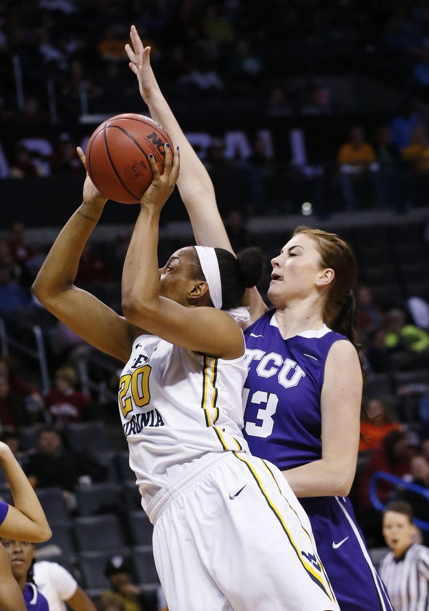West Virginia center Asya Bussie (20) shoots in front of TCU center Klara Bradshaw (13) during the first half of an NCAA college basketball game in the quarterfinals of the Big 12 Conference women's tournament in Oklahoma City, Saturday, March 8, 2014. West Virginia won 67-59. (AP Photo/Sue Ogrocki)