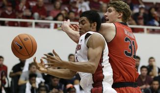 Stanford forward Josh Huestis, left, and Utah center Dallin Bachynski, right, battle for the ball during the first half of an NCAA college basketball game Saturday, March 8, 2014, in Stanford, Calif. (AP Photo/Eric Risberg)