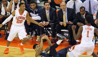 Pitt's Cameron Wright, center, tries to pass the ball as he falls on the floor between Clemson's Jordan Roper (20) and Austin Ajukwa (1) during an NCAA college basketball game at Littlejohn Coliseum in Clemson, S.C. on Saturday, Mar. 8, 2014. Pitt won in overtime, 83-78. (AP Photo/Anderson Independent-Mail, Mark Crammer) GREENVILLE NEWS - OUT; SENECA JOURNAL - OUT